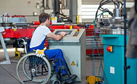 disabled worker in wheelchair in factory and his colleague
