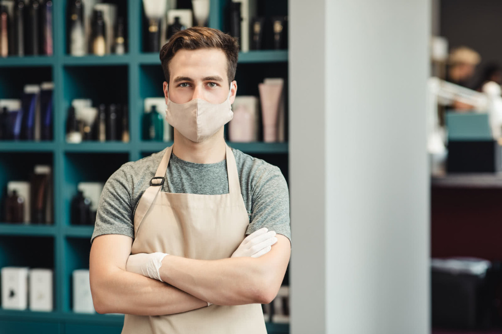 Portrait of confident barber posing in protective mask and apron in beauty salon interior, empty space